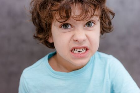Charming curly boy smiles. The boy lost the first milk tooth