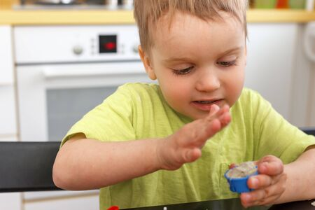 Cute little boy age of 3 years plays kinetic sand at home. Occupation with a child in quarantine. Stock fotó