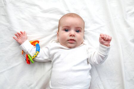 the baby smiles and lies in a white sweater on a white sheet, arms outstretched. Baby with beautiful blue eyes.