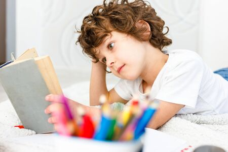 Close-up of a curly boy reads a thick book. The student is preparing for testing.