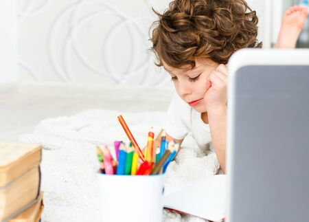 Curly Tired child does homework. Concept of difficulties of home schooling, distance studying