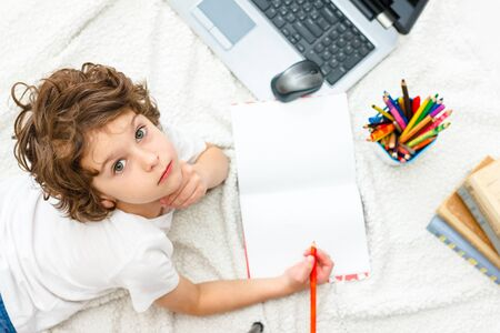 Curly boy is engaged at computer. schoolboy looks up, view into camera. Concept of difficulties of home schooling, distance studying