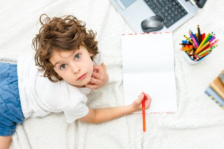 Curly boy is engaged at computer. schoolboy looks up. Concept of difficulties of home schooling, distance studying.