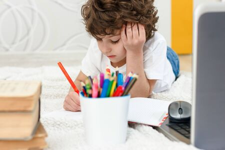 Curly boy is engaged at computer. schoolboy grabs his head in surprise. Concept of difficulties of home schooling, distance studying. Фото со стока