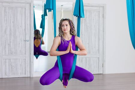Young beautiful woman doing aerial yoga practice in hammock in fitness club. Flying in hammock, butterfly pose.