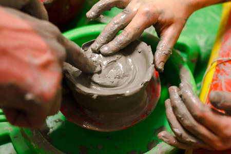 Close up childs hands works on a potters wheel, learns to work with clay.