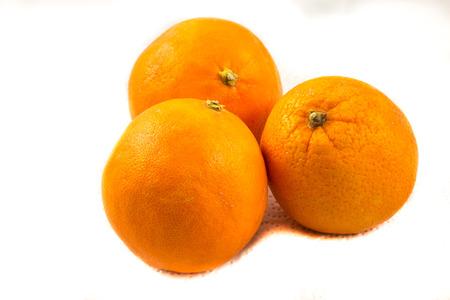 Drei Orangen auf Papier mit weißem Hintergrund Standard-Bild