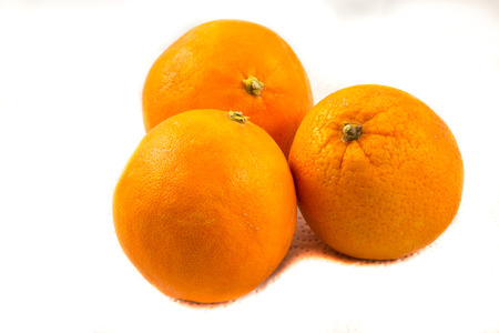 Three oranges on paper with white background
