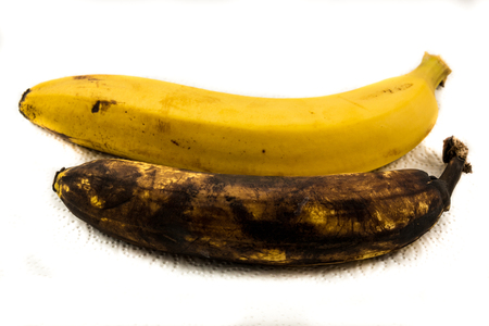 One yellow banana and one older brown banana on paper with white background Stock Photo