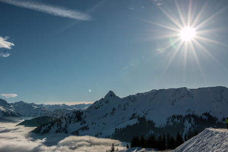 Snow and sun on the top of the mountains and fog down the valley Stock Photo