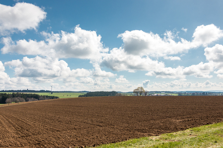 Big brown fields of fertile soil, green forest and wind power in the background