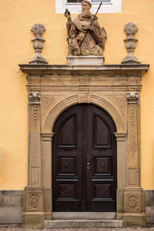 Old door of a historical building with statues and coats of arms made of stone Reklamní fotografie