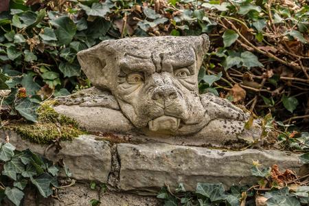 Little goblin head on a stone wall like out of a fairytale