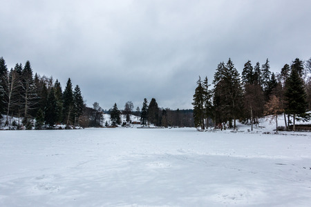 Frozen lake with ice and snow in winter