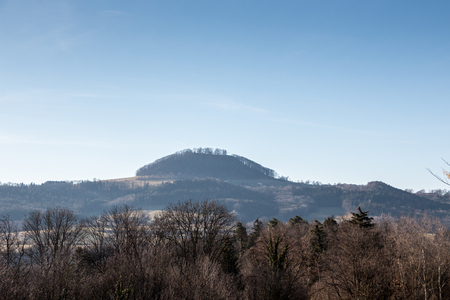 Little hill with forest and the blue sky