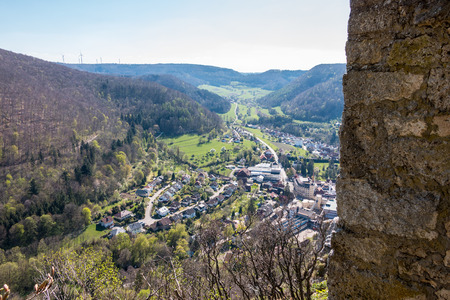 Little village in the middle of the german countryside with hills, forests, fields and meadows and the walls of a castle