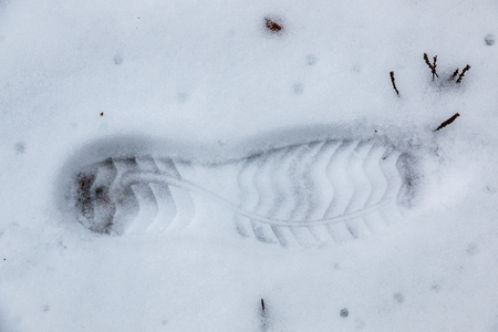 Foot print of a human shoe on the white snow Stock Photo