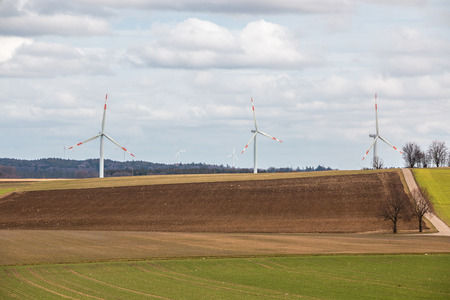 Big windmills for wind power near the village with fields and meadows
