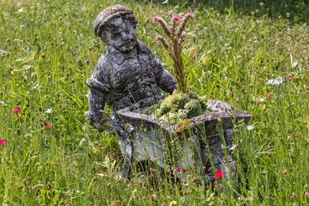 Farmer made of stone with a wheelbarrow on the middle of a wildflower meadow