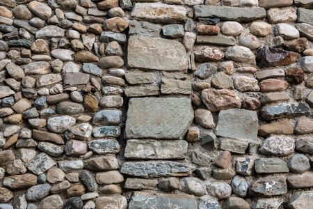 Natural stone wall with colorful and different sized stones