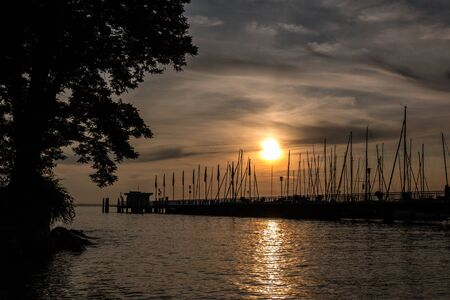 Golden sunset above the lake or the sea near the landing pier Banco de Imagens