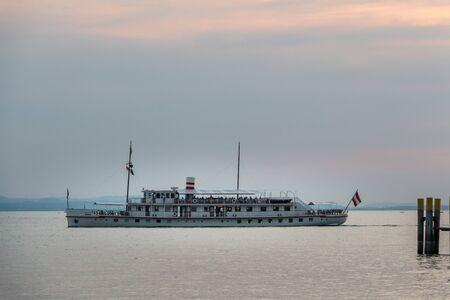 Ferryboat with passengers on the big lake Фото со стока