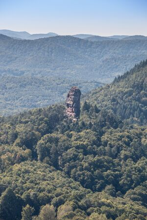 Big hill with a big rock and the green forest and the civilization Фото со стока