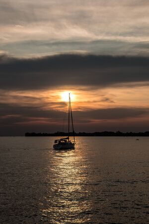 Black sailboat and a little black spit of land into the water and a golden sunset Banco de Imagens