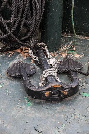 Old steel anchor on deck and black rope