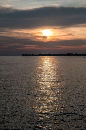 Petite langue noire de terre dans l'eau et un coucher de soleil doré Banque d'images