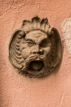 Stone head of a bearded man on an old building of the historical town