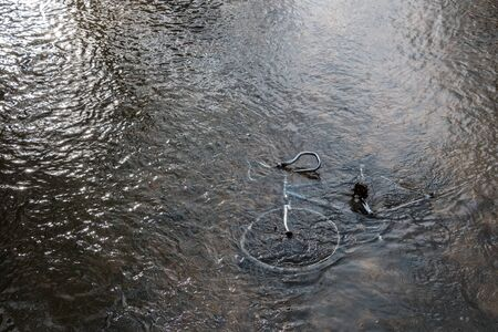 Steel bicycle strown into the river is pollution for environment Standard-Bild