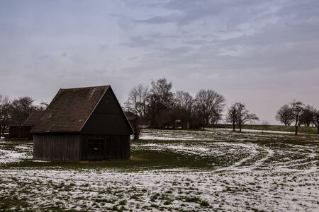 Brown cabin on the icy green field in winter