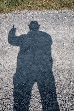 Black shadow of a man wearing a hat