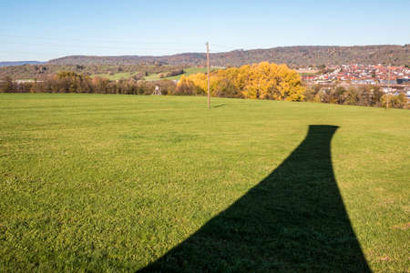 Black shadow of a tower on the green field . Standard-Bild
