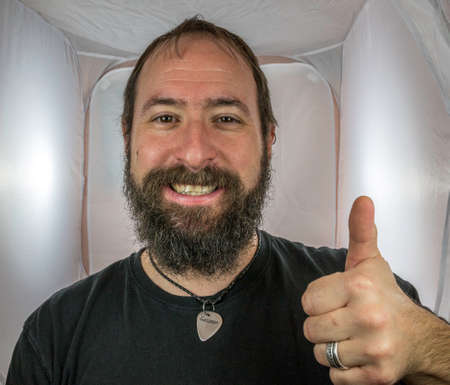 A bearded and smiling man showing respect and thumbs up