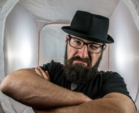 A bearded and angry looking man, looking like a doorkeeper with black glasses and hat