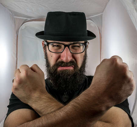 A bearded and angry looking man, looking like an artist or musician with black glasses and hat showing fist Standard-Bild