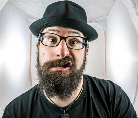 A silly looking bearded man with glasses and a black hat