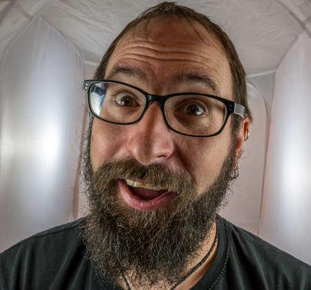 A surprised looking bearded man with glasses