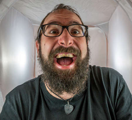 A bearded gleeful and gloating man in a good mood with black glasses Standard-Bild