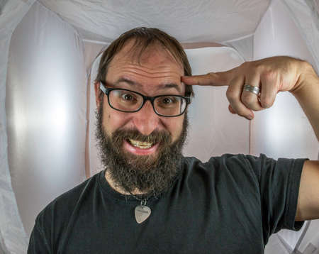 A bearded smiling man with black glasses has an idea Standard-Bild