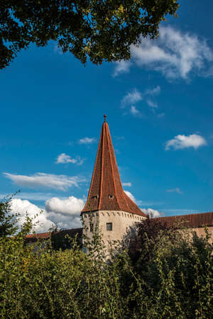Peaky city wall tower with trees and the blue cloudy sky Standard-Bild