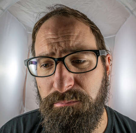 A bearded sad looking man in a depressive mood
