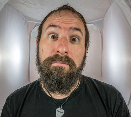 A bearded and surprised looking man with eyes wide open