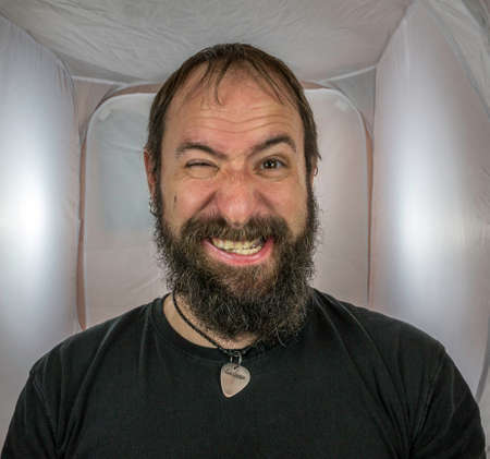 A bearded and silly looking man with one eye open