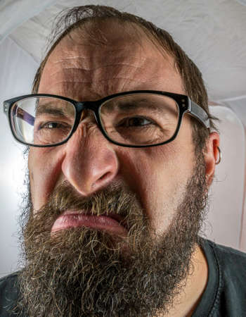 A bearded angry man with black glasses Standard-Bild