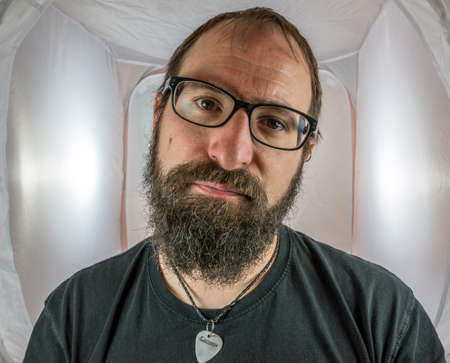 A bearded and annoyed looking man with black glasses