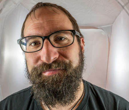 A bearded smiling man in a good mood with black glasses