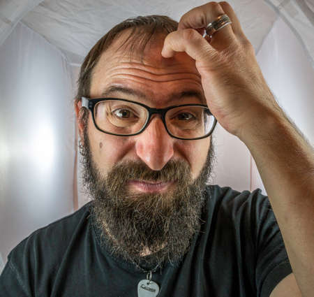 A bearded horrified looking man with black glasses